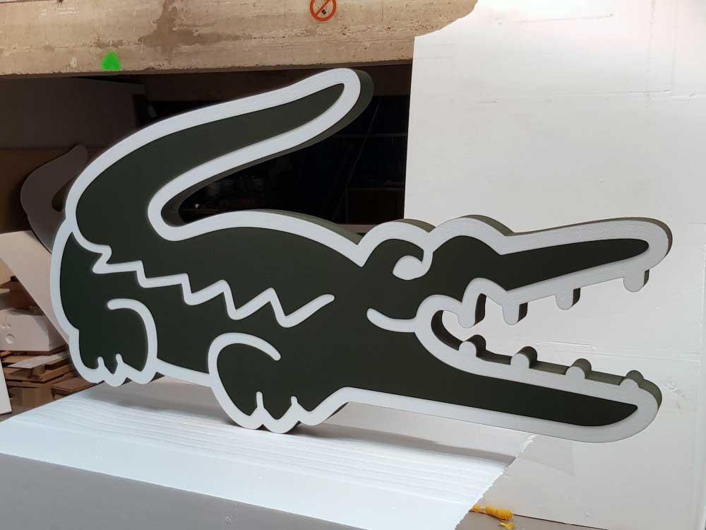 Découpe du logo Lacoste en polystyrène et PVC.