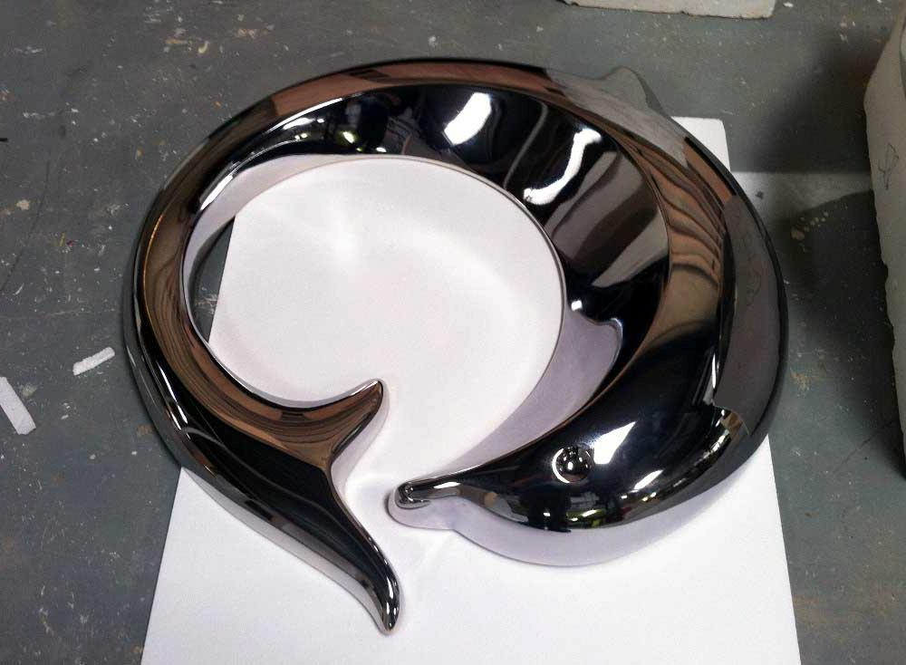 Fabrication d'un logo dauphin en polystyrène + projection de résine + peinture chrome.